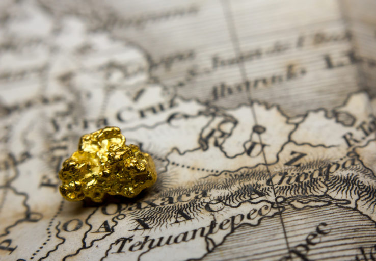 Close-up of a gold nugget on top of an old map of Mexico